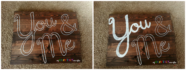 tracing and filling in the words on a rustic barn wood sign